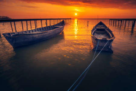 Two backlit fishing boats with the sun in the background at sunrise or sunset with some clouds on the sky and two wooden pontoons