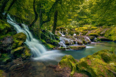 A big waterfall in deep forest in Nera Gorges Cheile Nerei in Romania 스톡 콘텐츠