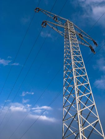 View of electrical tower in blue skies from below Stock Photo