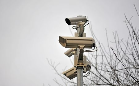 Four security cameras in front of a tree Stock Photo