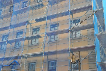 scaffolding covered with blue tarpaulin on an old building