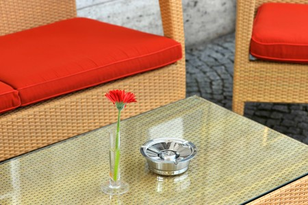 Hotel exterior with table, red chairs, red flower and ashtray