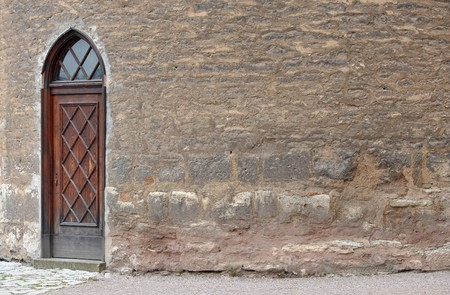 Old wooden door in an ancient brickwall of a castle photo