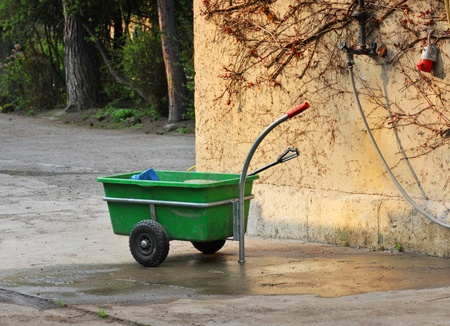 Green hand barrow for gardening on a court Stock Photo