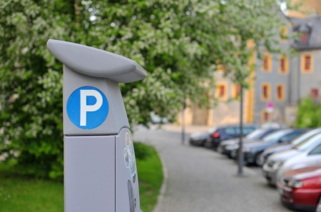 fee: Pay and display machine with parking area in the background Stock Photo
