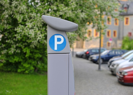 Pay and display machine with parking area in the background Stock Photo