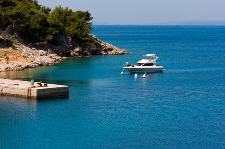 Small white yacht anchoring in a mediterranean bay, Croatia