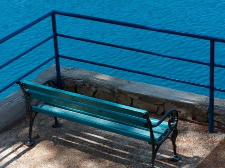Turquois bench and blue handrail at mediterranean sea