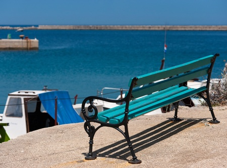 Empty Bench in front of a small mediterranean haven in croatia