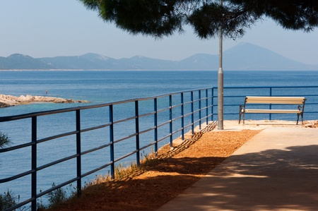 White empty bench with view over the Adriatic Sea and mountains of croatia in the background Stock Photo