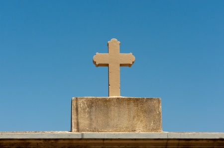 Old mediterranean christian cross made from stone against blue sky