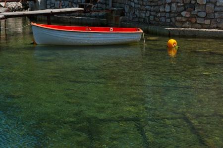 Red boat at a mediterranean harbor in Croatia Stock Photo