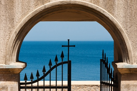 iron cross: Gate with cristian cross in front of the mediterranean sea