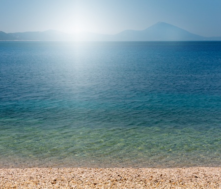 Beach of the adriatic sea with sun and mountains in the background Stock Photo