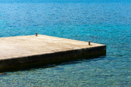Small dock from concrete at a mediterranean beach Stock Photo