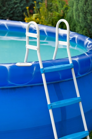 Detail of a blue portable swimming pool with a small ladder and water in it