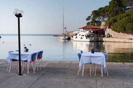 Tables of a small restaurant in a small mediterranean harbor in Croatia