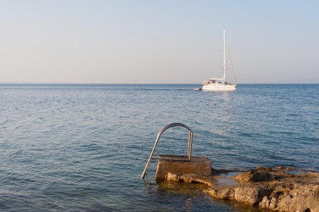 Stair for taking a bath in the rocky mediterranean sea in croatia with sailing boat in the background