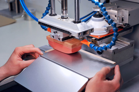imprenta: Alguien está trabajando con una impresora pad - imprimir en una lata