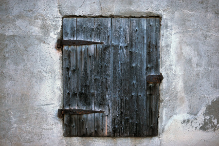 Ancient window with black wooden shutter and rusty brackets
