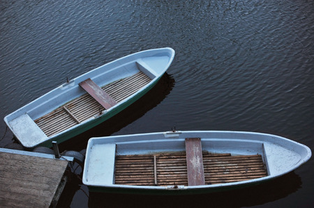 Two old rowing boats at jetty, footbridge