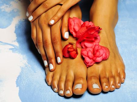 pedicura: Pies femeninos africanos y de la mano, pedicure azul con flores de color rosa de cerca