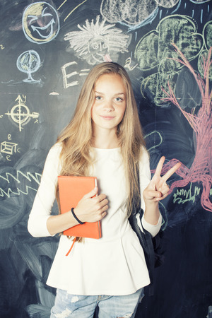 back to school after summer vacations, cute teen girl in classroom photo