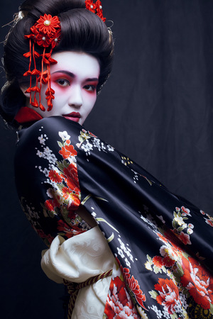 joven bastante geisha en kimono con sakura y decoración