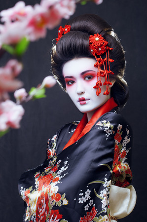 young pretty geisha in kimono with sakura and decoration photo