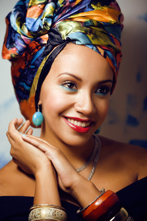 beauty bright african woman with creative make up, shawl on head like cubian woman closeup photo