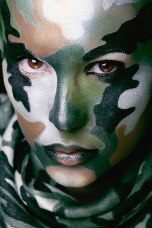 Beautiful young fashion woman with military style clothing and face paint make-up, khaki colors, halloween celebration photo