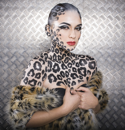 若いセクシーな女性ヒョウ猫ボディアートの全身メイクします。