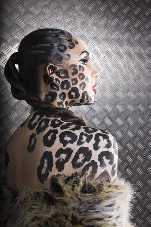 young  sexy woman with leopard make up all over body, cat bodyart photo