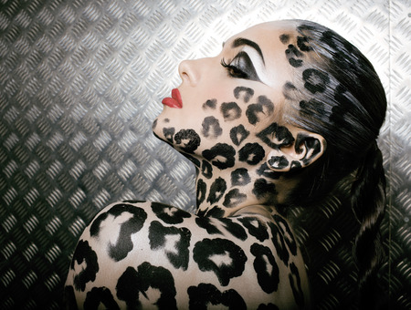 young  sexy woman with leopard make up all over body, cat bodyart Stock Photo