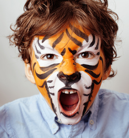 little cute boy with faceart on birthday party close up, little cute tiger Standard-Bild