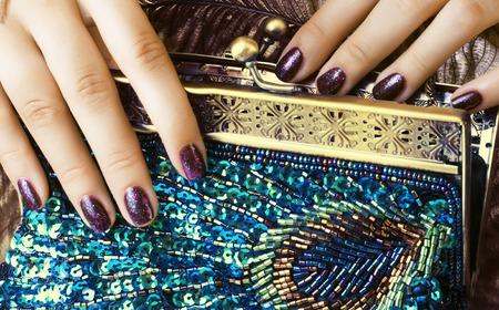 高級バッグを保持しているマニキュアと美容女性指