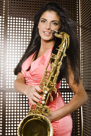 beauty young woman playing on saxophone at party photo