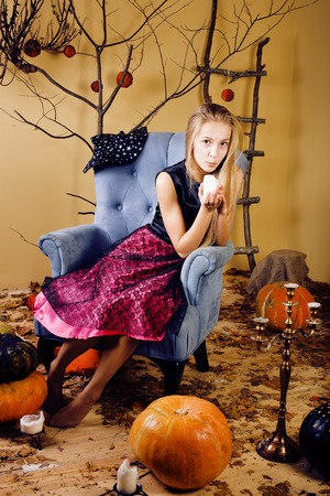 blond cute girl in halloween interior with pumpkin photo
