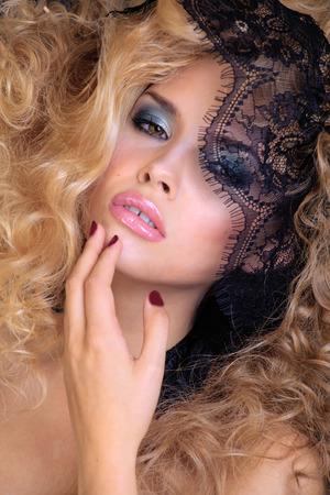 portrait of beauty blond young woman through lace close up photo