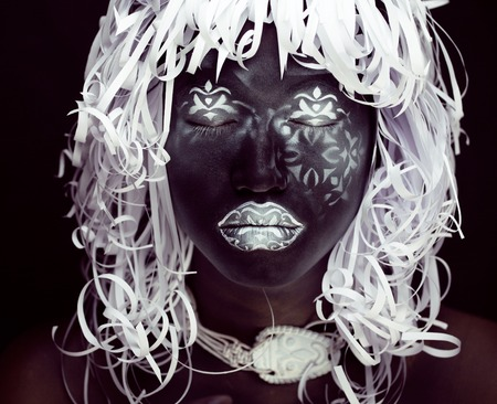 face close up: creative makeup like Ethiopian mask, white pattern on black face close up, halloween horror Stock Photo