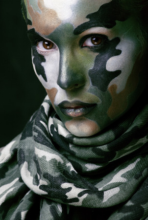 Beautiful young fashion woman with military style clothing and face paint make-up, khaki colors photo