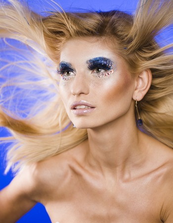 flying hair: beauty young blond woman with creative make up, flying hair