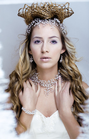 beauty young snow queen in fairy flashes with hair crown on her head photo