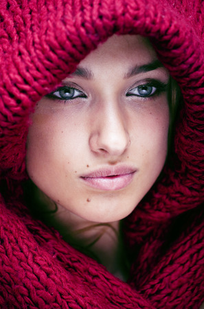 face close up: young pretty woman in sweater and scarf all over her face close up Stock Photo