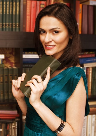 stock photo portrait of beauty young woman reading book in library smiling photo