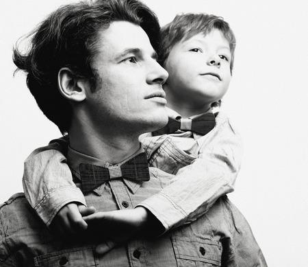 白地、カジュアルな蝶ネクタイで息子と父が家族を見てください。