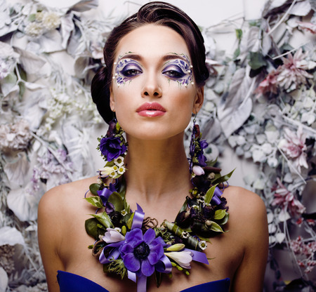 floral face art with anemone in jewelry, sensual young brunette woman close up photo