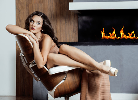 beauty yong brunette woman sitting near fireplace at home, winter warm evening in interior photo