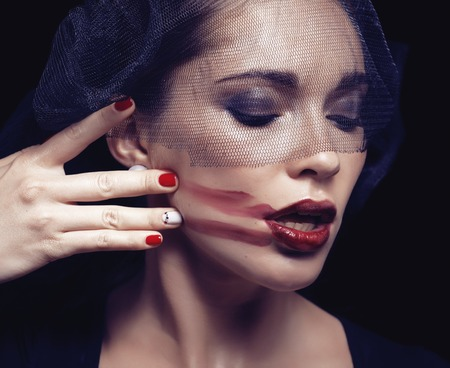 beauty brunette woman under black veil with red manicure close up, grieving widow, halloween makeup photo