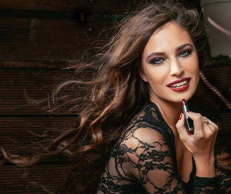 riches: beauty smiling rich woman in lace with dark red lipstick, flying hair close up